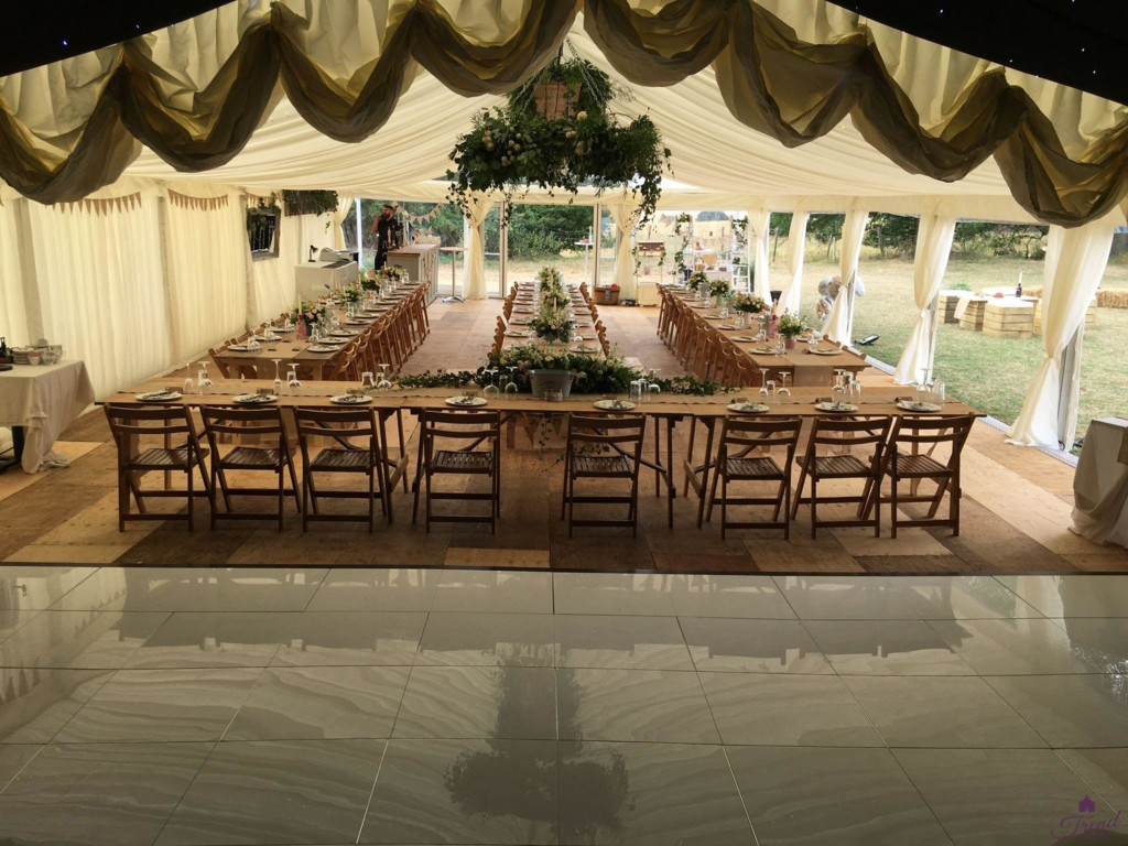 9m x 24m marquee lined in ivory with rustic banquet seating for 80 guests. Reveal curtain hides the dance floored area whilst dining