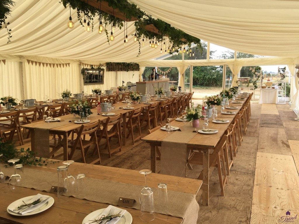 9m x 15m in ivory with rustic oak lighting, flooring and banquet seating for 80 guests, leading out to a 9m x 3m clear roof canopy