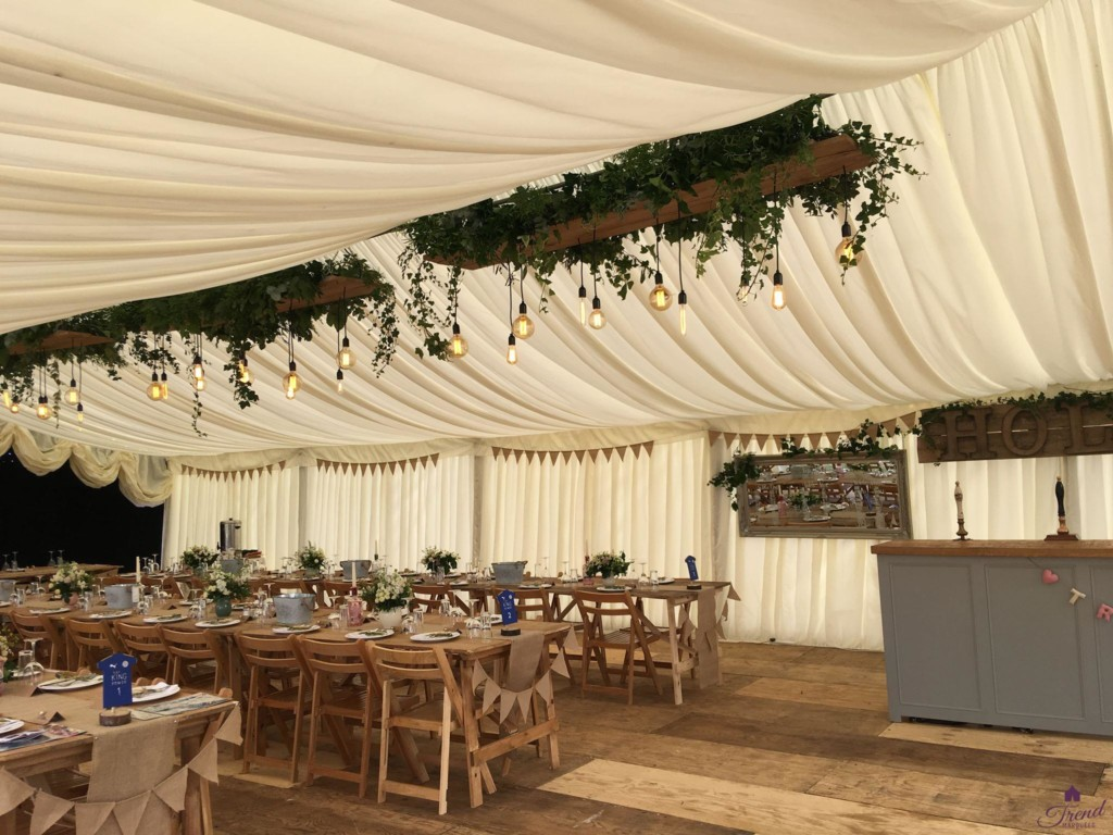 Marquee with classic ivory linings, rustic interior furnishings and oak topped bar