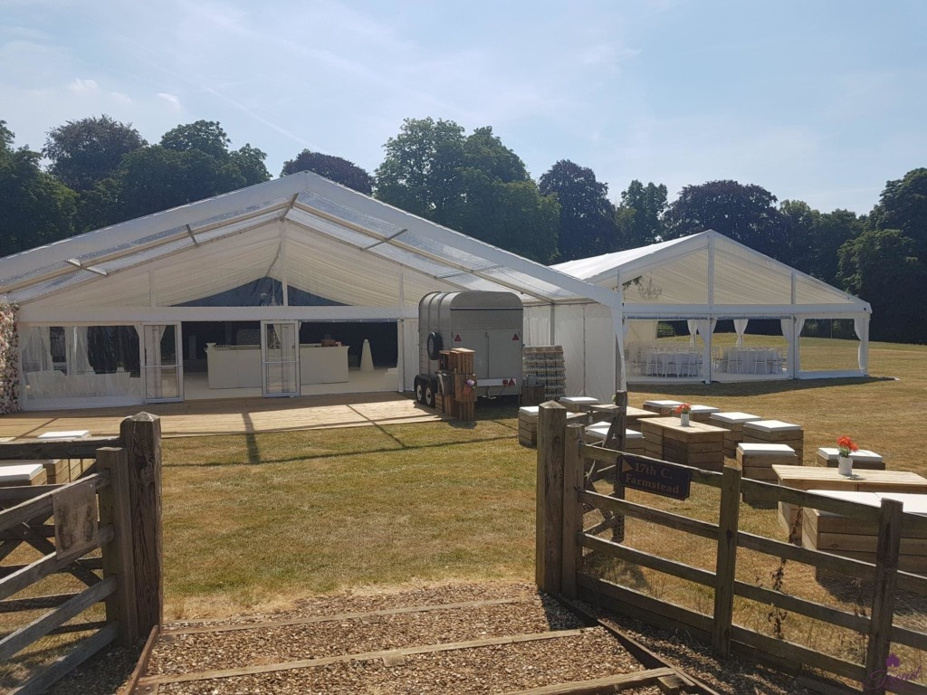 Entrance view of a 12m x 24m reception and entertainment marquee with 6m clear canopy conjoined with 12m x 18m dining marquee. An outdoor seating area using pallet furniture