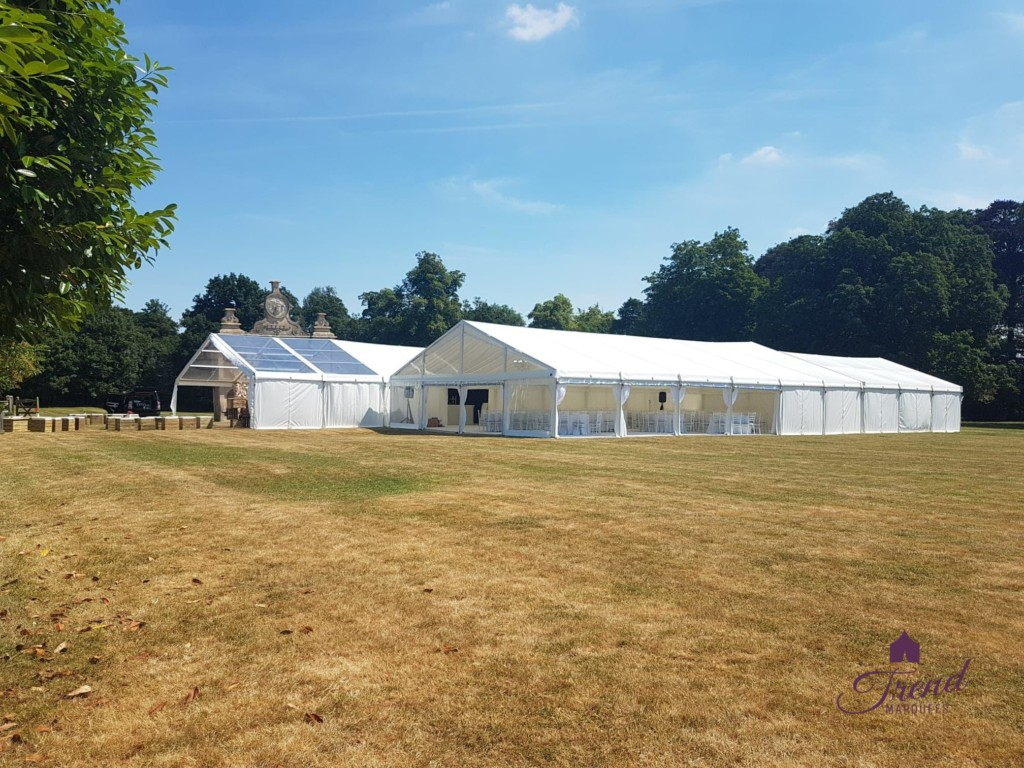 Side view of a 12m x 24m reception and entertainment marquee with 6m clear canopy conjoined with 12m x 18m dining marquee
