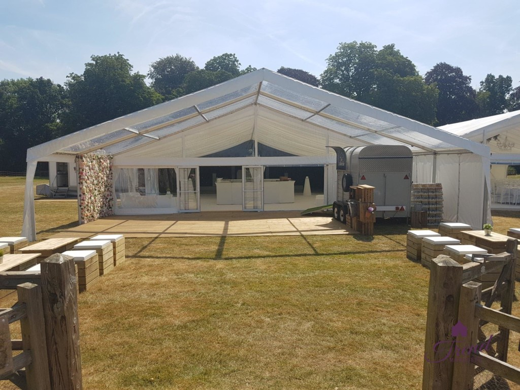 12m x 6m Clear canopy, decked entrance marquee with flower wall and gin bar. An outdoor seating area using pallet furniture