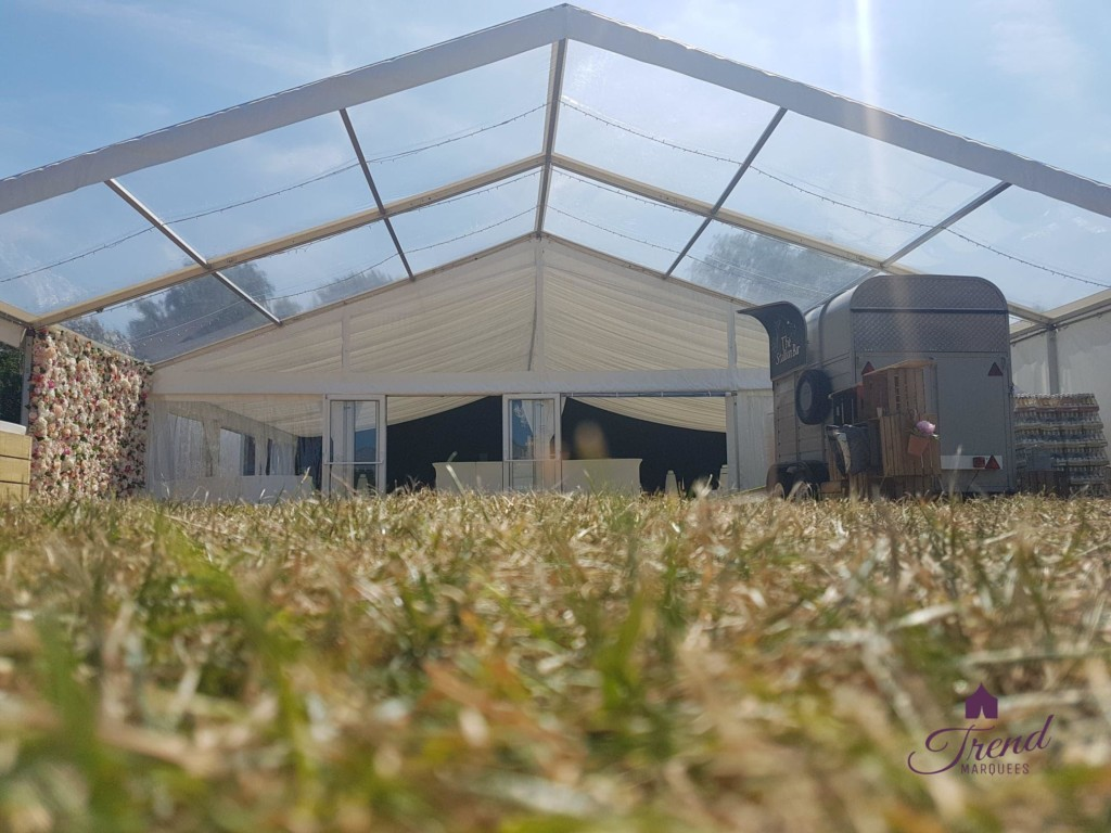 12m x 6m Clear canopy, with fairy lights, flower wall and gin bar.