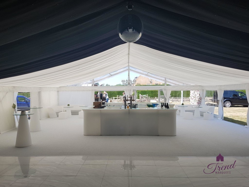 DJ View of 12m x 18m reception and entertainment marquee. Lined with half black starlight and half white, clear end gable and clear roof porch. Furnished with a square LED bar, LED furniture and an all white dance floor